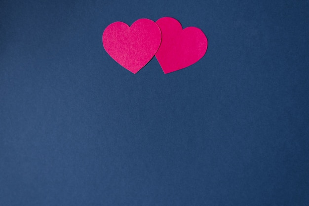 Two pink hearts on a dark blue background with copying . pattern for valentine's day. holiday card for the day of love. origami