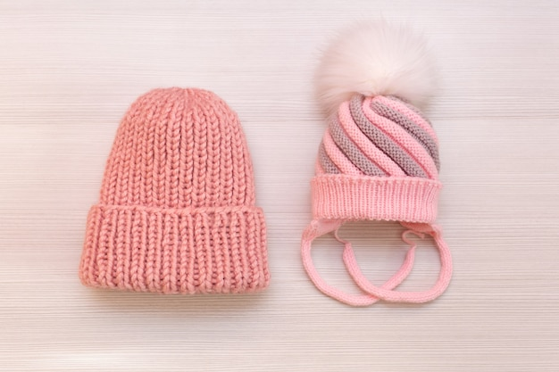 Two pink knitted hats on a white background