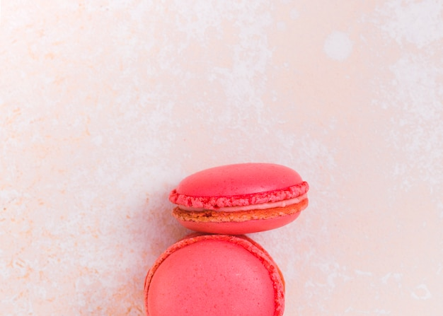 Two pink macaroons on textured background