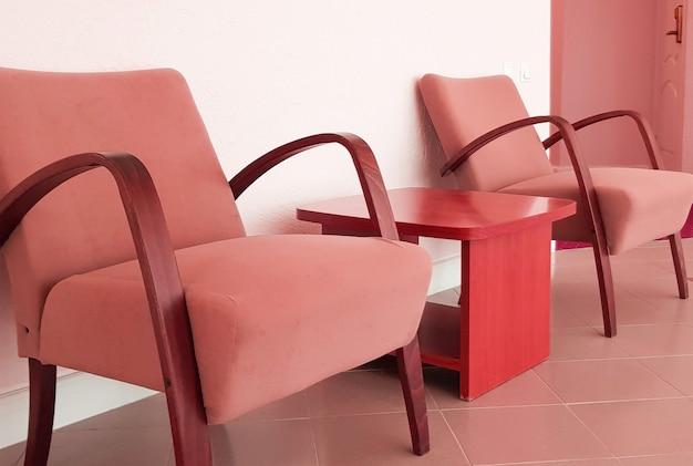 ピンクの壁にピンクレッドのアームチェア2脚とその間にあるコーヒーテーブル、リビングルームまたはホテルのロビーのモダンなインテリア。
