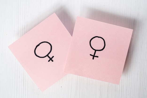 Two pink stickers with gender symbols venus on white background