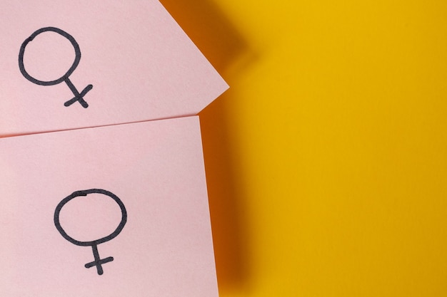 Two pink stickers with the gender symbols venus above yellow background