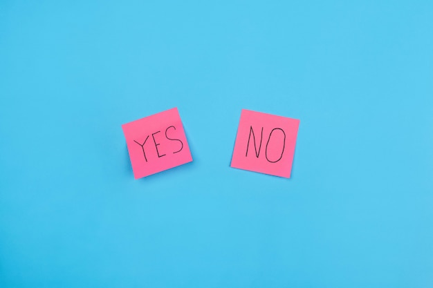 Two pink stickers with phrase yes or no on a blue . close-up. free space for notes.