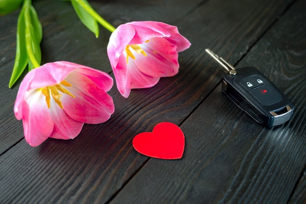 Two pink tulip flowers, car keys and red paper heart lie on dark wooden table.