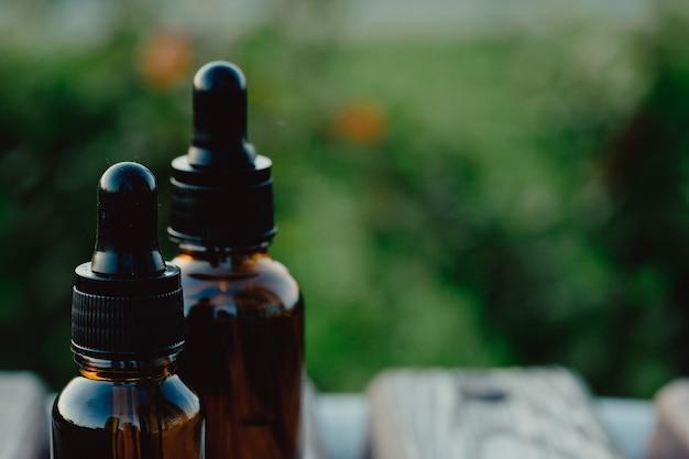 自然の背景に2つのピペットとエッセンシャルオイルのボトル。スポイトボトルのモックアップ-2本。