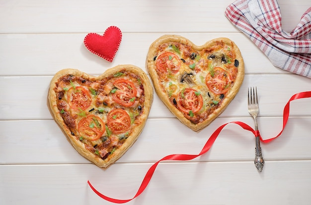 Two pizza in the form of a heart on a white wooden table with a fork with a red ribbon with a red heart. romantic dinner for valentine's day, love.