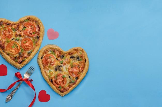 コピースペースのある赤いハートの青いテーブルにハートの形をした2つのピザ。バレンタインデーのロマンチックなディナーにピザを注文してください。愛。