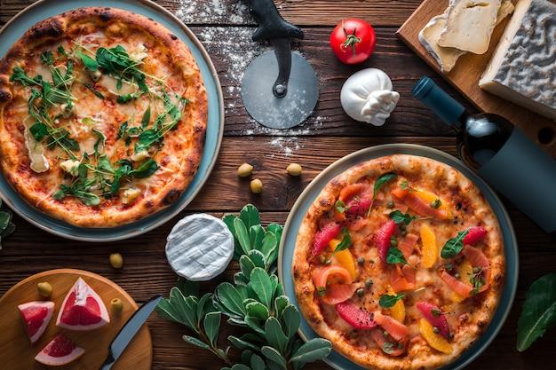 木製の背景、平面図、コピー領域にある大皿に2つのピザ。 1つはチーズのピザ、もう1つは魚とグレープフルーツのピザ。