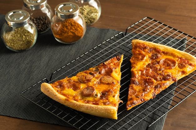 黒い布のプレースマットの冷却ラックの場所にペパロニをトッピングした2つのピザと、コナーの瓶にハーブとスパイスのグループ