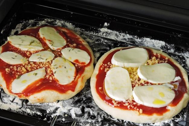 焼く前にベーキング トレイにモッツァレラチーズのピザ マルガリータ 2 枚