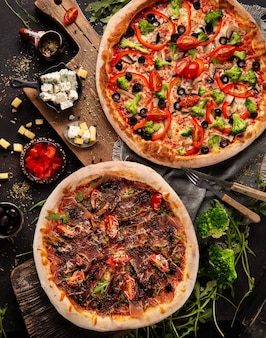 Две пиццы на деревянном шкафу и несколько ингредиентов и специй вокруг