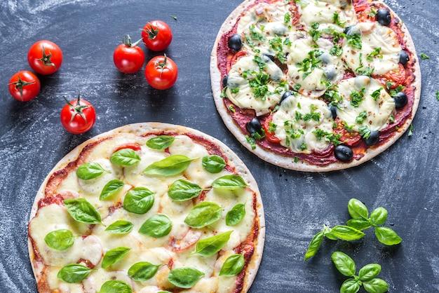 Две пиццы с ингредиентами на деревянной поверхности