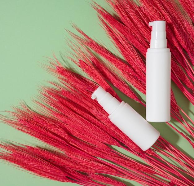 붉은 밀이 있는 녹색 배경에 화장품용 디스펜서가 있는 플라스틱 병 2개. 크림, 젤, 혈청, 광고 및 제품 판촉용 포장, 평면도