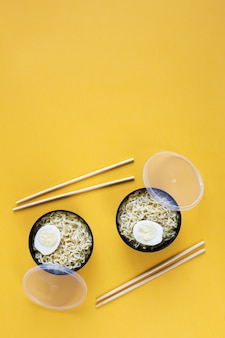 계란과 젓가락 평면 인스턴트 국수의 두 플라스틱 그릇 복사 공간이 노란색 종이 배경에 누워