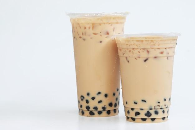 Два пластиковых стакана тайваньского ледяного чая с молоком с пузырем боба, сладкий напиток, большой и маленький пластиковый стаканчик на белом фоне, концепция напитков и еды