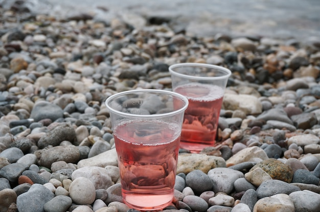 Two plastic glasses filled with rose wine on shingle beach