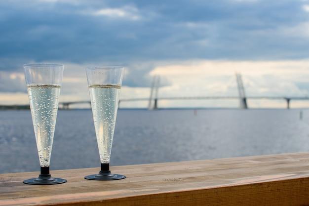 街の背景、大きな橋、海、暗い空の木製の表面にスパークリングシャンパンの2つのプラスチックグラス。