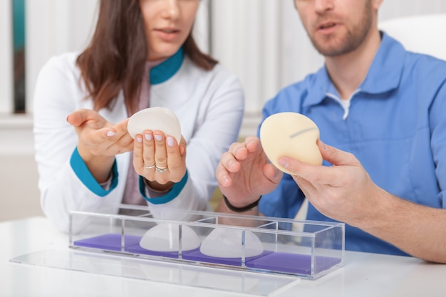 Two plastic surgeons discussing silicone breast implants