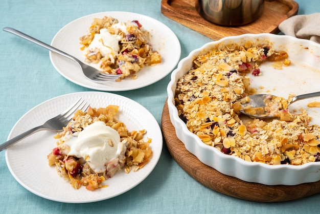 Two plate with apple and pear crumble with ice cream streusel sweet dessert side view