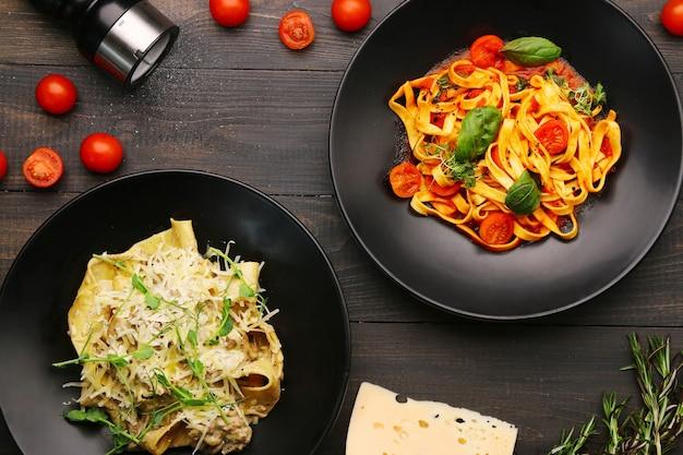 Две тарелки с видом сверху макаронных изделий. паста альфредо с говядиной и пастой маринара на деревянном столе с ингредиентами, перцем и сыром.