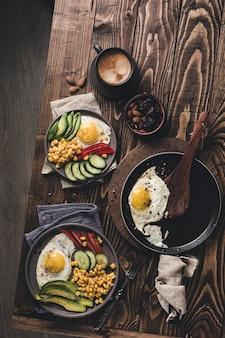 Две тарелки и сковорода с вареными яйцами с авокадо, перцем, огурцом и консервированной кукурузой на темном деревянном фоне. здоровый завтрак. вид сверху с copyspace. плоская планировка.