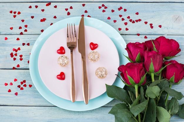 Две тарелки, столовые приборы, букет роз и сердечки