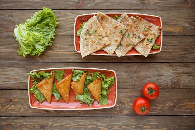 Two plates of flatbread wraps gutab and triangular borek