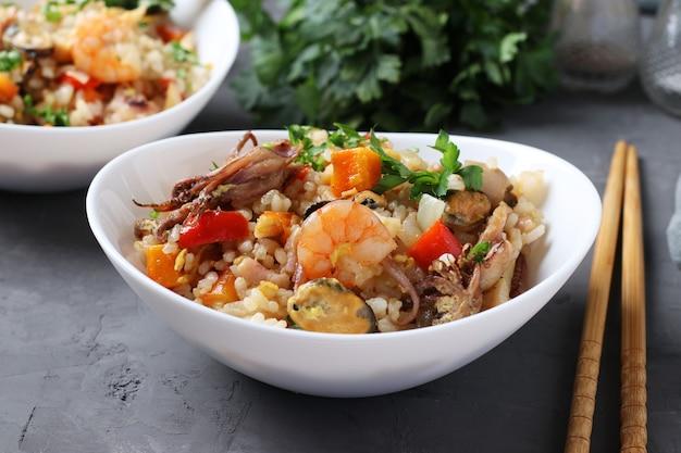 Две тарелки жареный рис с морепродуктами, овощами, имбирем и петрушкой на темном фоне. азиатская кухня. вегетарианская пища. крупный план. горизонтальный формат