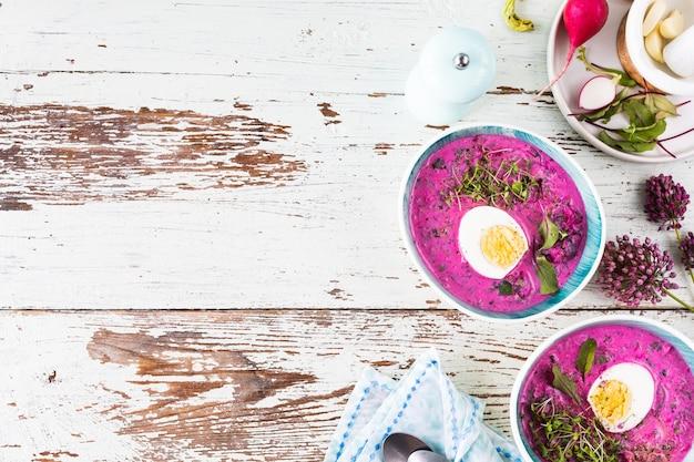 木製のテーブルの上に寒い夏のビートルート、キュウリ、卵のスープの2つのプレート。上面図。スペースをコピーします。