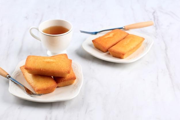 新鮮なバターを添えたおいしいフランスのフィナンシェケーキの2つのプレート、お茶を添えて。 financierはバターケーキです。テキスト用のコピースペース