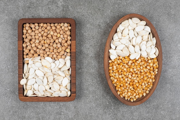 Due piatti di mais crudo, piselli e semi di zucca su marmo.