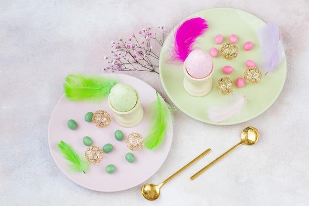2つのプレート、2つの卵、スプーン、イースターの装飾
