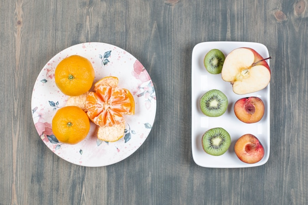 Two plates of various fruits on wooden surface