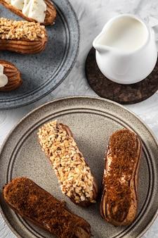 テーブルの上に自家製エクレアと白いクリームボウルが付いた2つのプレート、ミルクドリンク付きの艶をかけられたパティスリー