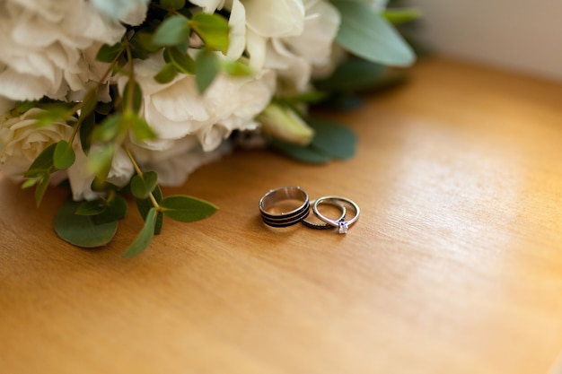 Two platinum wedding rings on wood with flowers