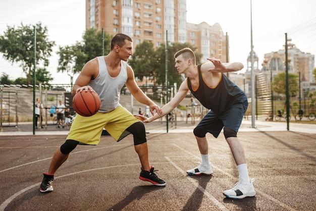 야외 코트에서 농구장 중앙에 두 선수.
