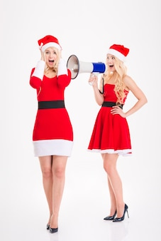 Two playful blonde sisters twins in dresses of santa claus having fun with megaphone over white background