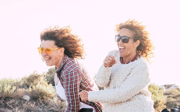 2 人の遊び心のある幸せな陽気な中年女性は、一緒に遊ぶのがとても楽しいです。