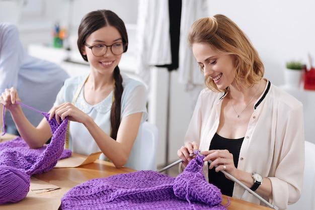 테이블에 앉아 보라색 실로 스카프를 뜨개질하고 즐거운 것을 논의하는 두 명의 즐거운 쾌활한 여성