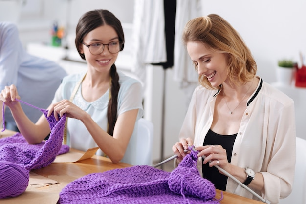Two pleasant cheerful women sitting at the table and knitting scarves with purple threads and discussing something pleasant