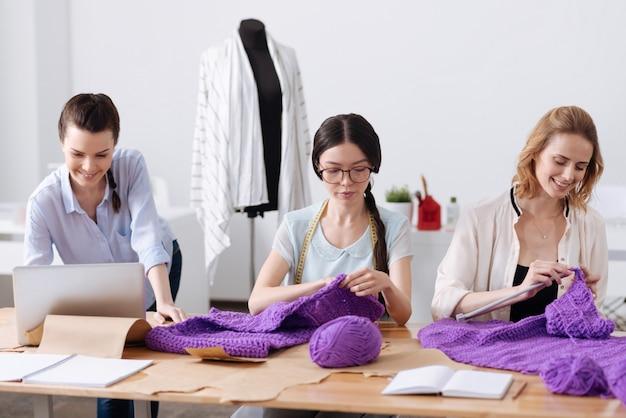 동료가 랩톱에서 작업하는 동안 테이블에 앉아 보라색 실로 스카프를 뜨개질 두 즐거운 예쁜 여자
