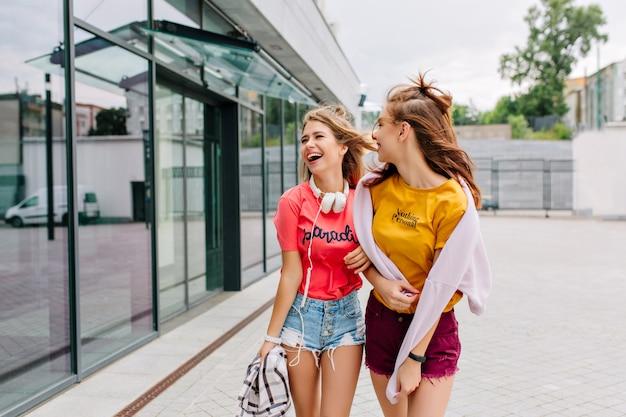 Due ragazze soddisfatte in abiti luminosi che parlano e cercano di mostrare, godendosi il fine settimana insieme