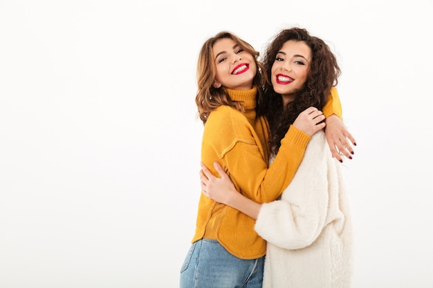 Two pleased girls in sweaters hugging to each other  over white wall