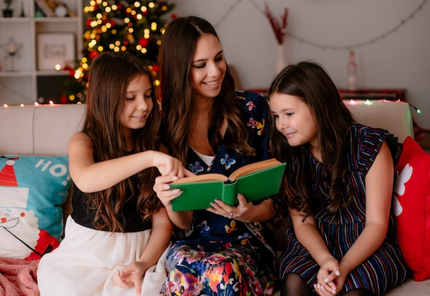 Two pleased sisters and young smiling mother at home at christmas time sitting on sofa in living room mother reading book to daughters looking at elder daughter younger one pointing at book