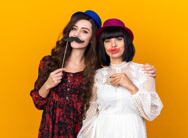 Due giovani donne contente che indossano un cappello da festa guardando davanti, tenendo baffi e labbra finti