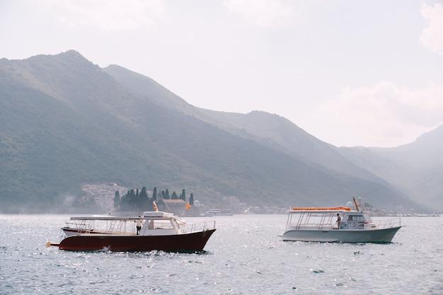ペラストの街の山と島々を背景にした2つのプレジャーモーターボート