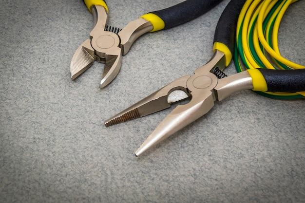 マスターが電気を修理するために、灰色の背景にある電気技師用の2つのペンチツールとワイヤーを使用