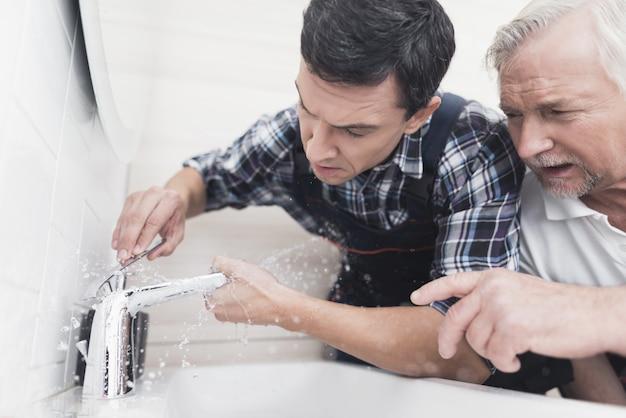 Two plumbers are repairing faucet in bathroom.