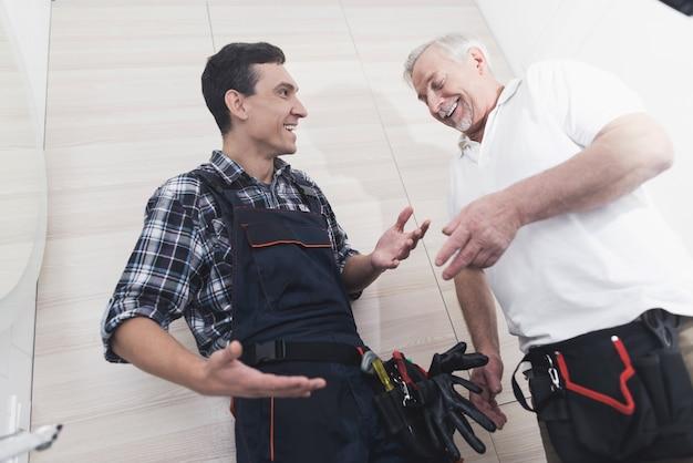 Two plumbers repair the faucet in the bathroom