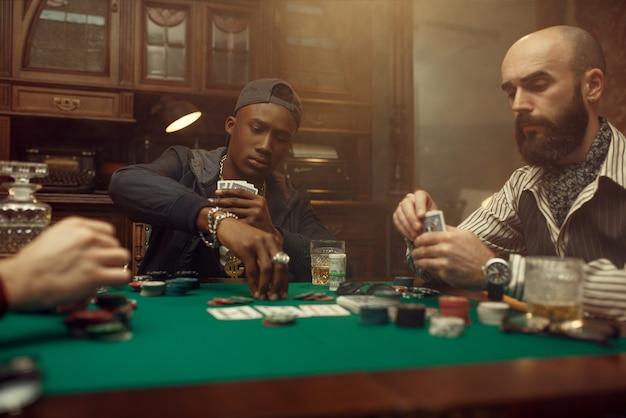 두 명의 포커 플레이어가 카지노에서 녹색 천으로 게임 테이블에 베팅을합니다. 중독, 위험, 도박장